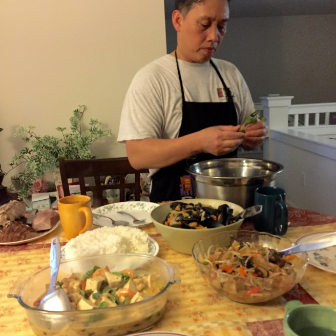 My father garnishing with Thai Basil. All of that food is just for me, my mother, and him. Always incredible.